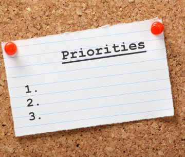 A blank list of Priorities on a paper note pinned to a cork notice board. In business and in life we draw up lists of actions to aid us in getting things done.